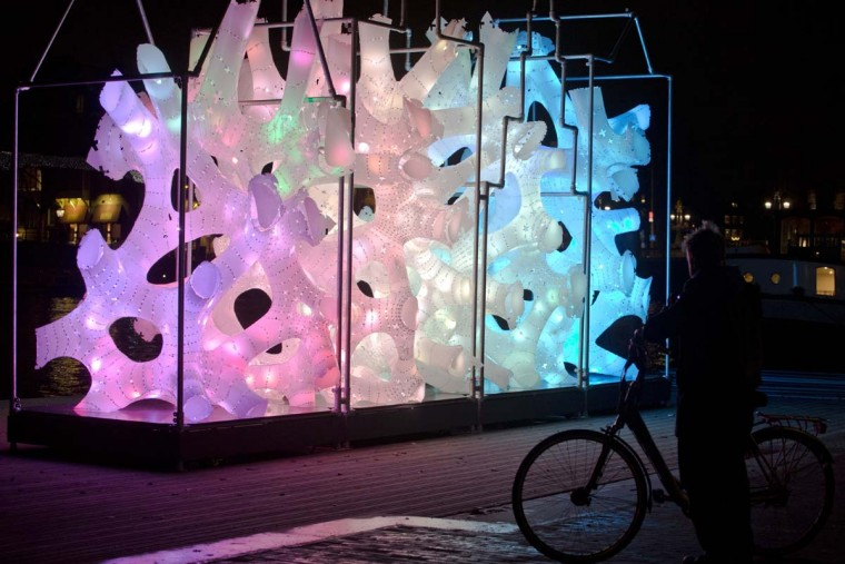 """A bicyclist stops to look at """"Rhizome House"""", an art work by Singapore's DP Architects, part of the Amsterdam Light Festival, Netherlands, Wednesday, Nov. 30, 2016. The festival opens on Dec. 1, 2016, and ends on Jan. 22, 2017, the artworks are lit from 17:00 until 23:00, and for the Illuminade, a walking route, between 17:00 and 22:00 Central European Time. (AP Photo/Peter Dejong)"""