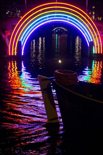 """A boat passes """"Bridge of the Rainbow"""", an art work by French light designer Gilbert Moity, part of the Amsterdam Light Festival, Netherlands, Wednesday, Nov. 30, 2016. The festival opens on Dec. 1, 2016, and ends on Jan. 22, 2017, the artworks are lit from 17:00 until 23:00, and for the Illuminade, a walking route, between 17:00 and 22:00 Central European Time. (AP Photo/Peter Dejong)"""