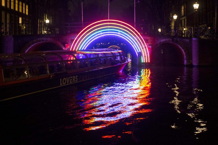 """A canal cruise boat passes under """"Bridge of the Rainbow"""", an art work by French light designer Gilbert Moity, part of the Amsterdam Light Festival, Netherlands, Wednesday, Nov. 30, 2016. The festival opens on Dec. 1, 2016, and ends on Jan. 22, 2017, the artworks are lit from 17:00 until 23:00, and for the Illuminade, a walking route, between 17:00 and 22:00 Central European Time. (AP Photo/Peter Dejong)"""