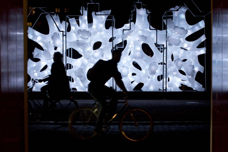 Two bicyclists pass Rhizome House, an art work by Singapore's DP Architects, part of the Amsterdam Light Festival, Netherlands, Wednesday, Nov. 30, 2016. The festival opens on Dec. 1, 2016, and ends on Jan. 22, 2017, the artworks are lit from 17:00 until 23:00, and for the Illuminade, a walking route, between 17:00 and 22:00 Central European Time. (AP Photo/Peter Dejong)