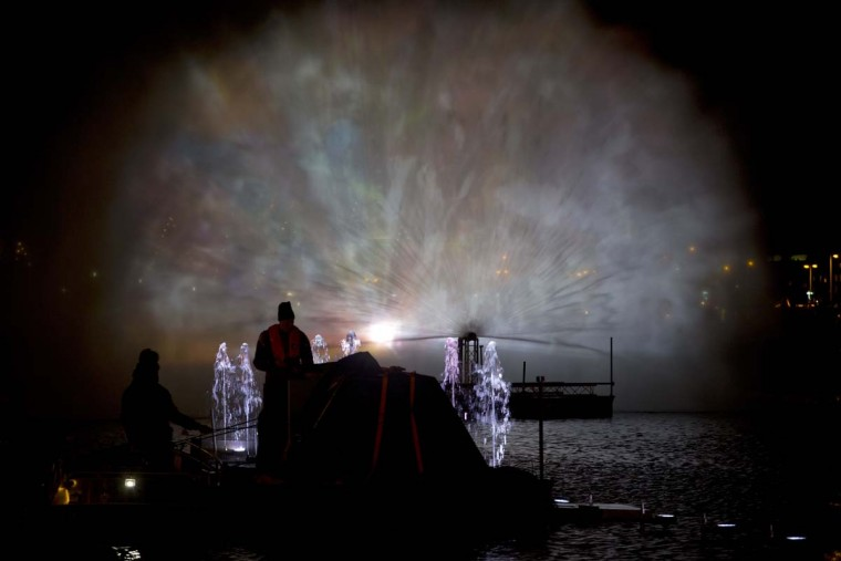 A man watches Arco, an art work by Austrian artist Teresa Mar, with projections on water spray, as part of the Amsterdam Light Festival, Netherlands, Wednesday, Nov. 30, 2016. The festival opens on Dec. 1, 2016, and ends on Jan. 22, 2017, the artworks are lit from 17:00 until 23:00, and for the Illuminade, a walking route, between 17:00 and 22:00 Central European Time. (AP Photo/Peter Dejong)