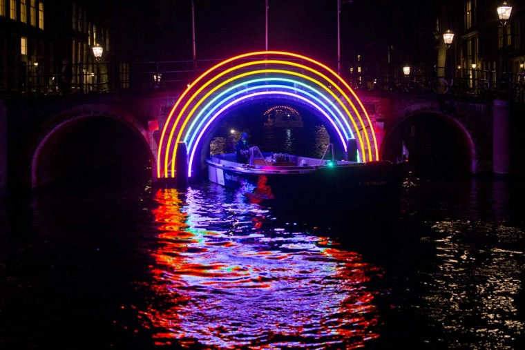 """A boat passes under """"Bridge of the Rainbow"""", an art work by French light designer Gilbert Moity, part of the Amsterdam Light Festival, Netherlands, Wednesday, Nov. 30, 2016. The festival opens on Dec. 1, 2016, and ends on Jan. 22, 2017, the artworks are lit from 17:00 until 23:00, and for the Illuminade, a walking route, between 17:00 and 22:00 Central European Time. (AP Photo/Peter Dejong)"""
