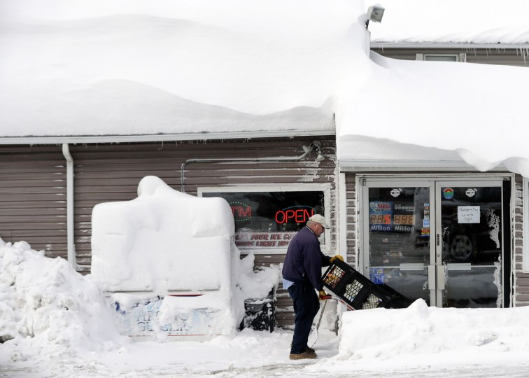 Bob Fox delivers milk to Grafton's Town Store, as he walks through lake-effect snow on the ground, Monday, Nov. 21, 2016, in Grafton, N.Y. (AP Photo/Mike Groll)
