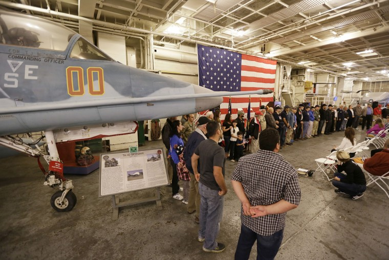 Service members stand while being recognized during a Veterans Day ceremony on the hangar deck of the USS Hornet Museum Friday, Nov. 11, 2016, in Alameda, Calif. The Essex-class carrier is known for its service in World War II and the recoveries of the Apollo 11 and 12 lunar capsules after astronauts walked on the moon. (AP Photo/Eric Risberg)