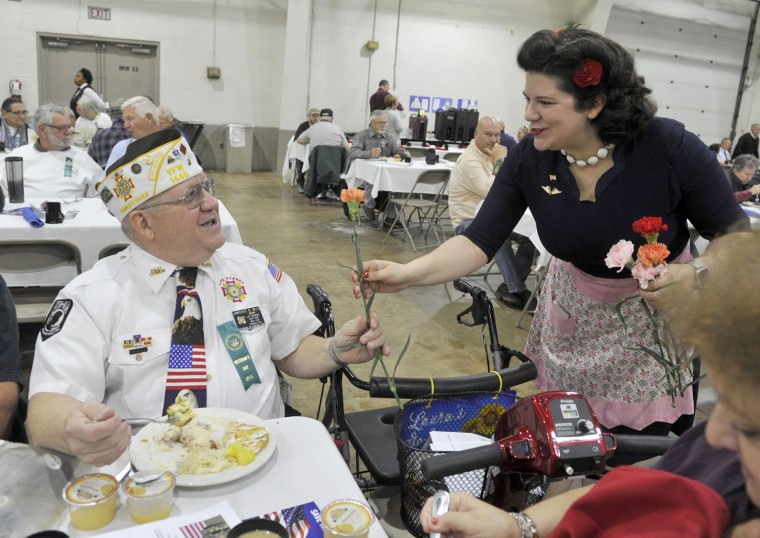 Volunteer Christine Cooper presents a carnation to veteran Lawrence Wills before the York County Veterans Day program in Memorial Hall West at the York Expo Center in York, Pa. on Friday, Nov. 11, 2016. (Jason Plotkin/York Daily Record via AP)
