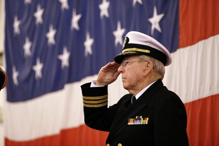 Chaplain Wallace Whatley salutes as the national anthem is played during a Veterans Day ceremony on the hangar deck of the USS Hornet Museum Friday, Nov. 11, 2016, in Alameda, Calif. The Essex-class carrier is known for its service in World War II and the recoveries of the Apollo 11 and 12 lunar capsules after astronauts walked on the moon. (AP Photo/Eric Risberg)