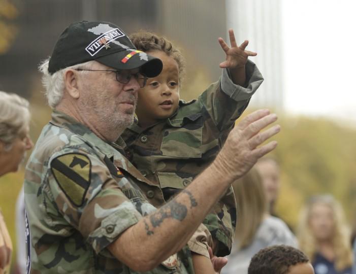 Vietnam veteran Robert Hullihan and his grandson, Jeremiah Johnson, 2, wave while attending a Veterans Day parade in Sacramento, Calif., Friday, Nov. 11, 2016. (AP Photo/Rich Pedroncelli)