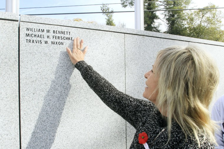Robin Ferschke touches the name of her son Michael H. Ferschke that is engraved into the wall of the Blount County War Dead Memorial, Friday, Nov 11, 2016, during the 48th Veterans Day Program at Blount County Courthouse in Maryville, Tenn. (Mark A. Large/The Daily Times via AP)
