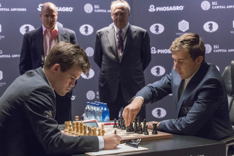 Challenger Sergey Karjakin, right, of Russia, makes a move against chess world champion Magnus Carlsen, of Norway, during the first round of the World Chess Championship, Friday, Nov. 11, 2016, in New York. (AP Photo/Mary Altaffer)