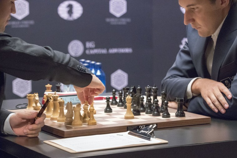 Chess world champion Magnus Carlsen, left, of Norway, makes a move against challenger Sergey Karjakin, of Russia, during the first round of the World Chess Championship, Friday, Nov. 11, 2016, in New York. (AP Photo/Mary Altaffer)