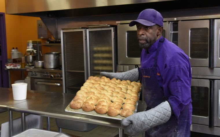 "James Hamlin, owner of The Avenue Bakery, pulls a tray of his famous ""Poppay's"" wheat dinner rolls from the oven. (Barbara Haddock Taylor/Baltimore Sun)"