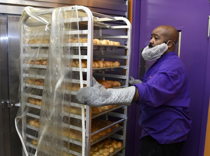 "James Hamlin, whose father James W. Hamlin owns The Avenue Bakery, pulls a cart with the bakery's famous ""Poppay's"" dinner rolls that are ready to be boxed. (Barbara Haddock Taylor/Baltimore Sun)"