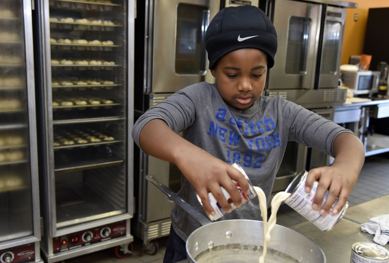 "James ""L. J."" Hamlin, grandson of owner James Hamlin, pours ingredients into a pot for his grandfather's famous dinner rolls. L.J. hopes to run the bakery some day, he said. (Barbara Haddock Taylor/Baltimore Sun)"