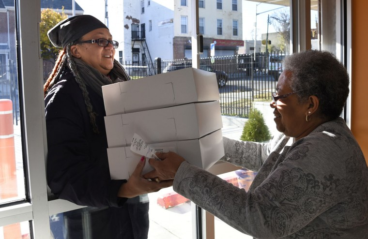 "Toni Vonder Haar, left, of Baltimore picks up her order of 3 dozen ""Poppay's"" dinner rolls from Brenda Hamlin, right, wife of owner James Hamlin of The Avenue Bakery. (Barbara Haddock Taylor/Baltimore Sun)"