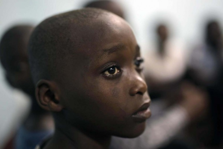 """In this photo taken on Saturday, June 18, 2016, Moise Bahati, 12, joins other street children in a prayer service at a Don Bosco safe house in Goma, Democratic Republic of Congo. Bahati, who left home fleeing from domestic violence, has been in the shelter for 5 months. """" This is much better than home, i do not want to go back"""" he said. (AP Photo/Jerome Delay)"""