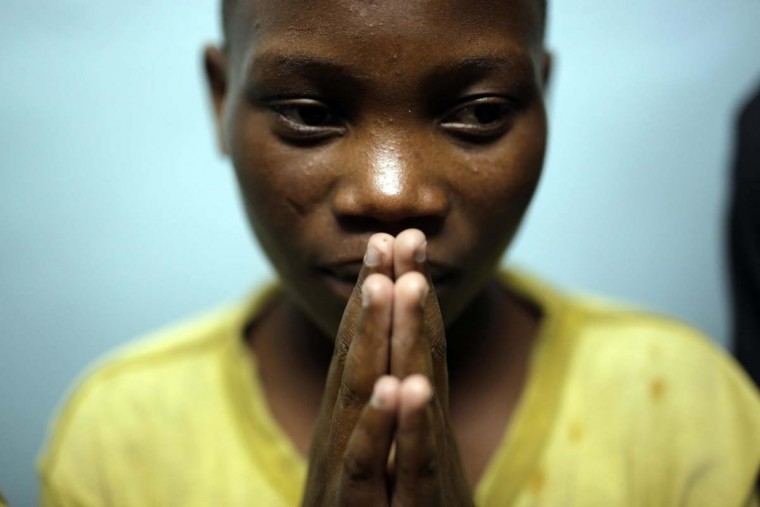 """In this photo taken on Saturday, June 18, 2016, Jean Claude Twisenge, 15, from Massissi, joins other street children in a prayer service at a Don Bosco safe house in Goma, Democratic Republic of Congo. Jean Claude had walked for a week to reach Goma, """"Fleeing misery, I was looking for money to pay for school"""". (AP Photo/Jerome Delay)"""
