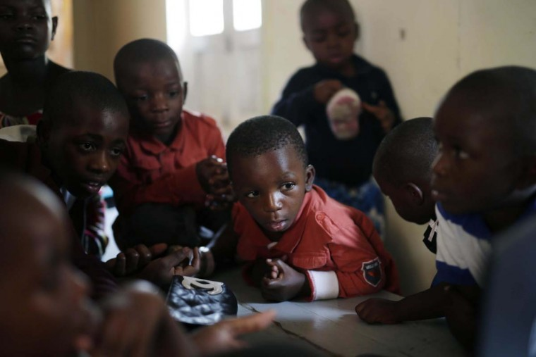 In this photo taken on Sunday, June 19, 2016, orphan children watch a film on a portable computer at the En Avant Les Enfants INUKA center in Goma, Democratic Republic of Congo. More than four million children have lost at least one parent in Congo over the past two decades.(AP Photo/Jerome Delay)
