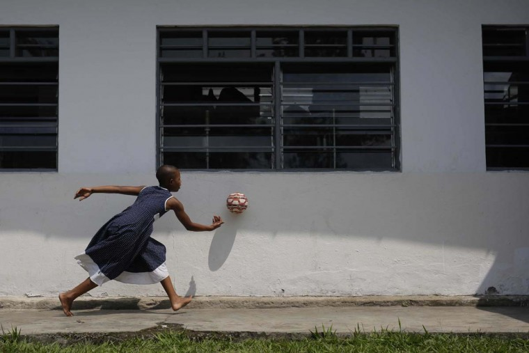 In this photo taken on Sunday, June 19, 2016, ten-year-old Safina Gatuku, plays with a ball at the En Avant Les Enfants INUKA center in Goma, Democratic Republic of Congo. Abandoned by their father, Safina and her sister Subiza, eight, walked two days in the forest after their mother was killed by soldiers in 2009 before being pick-up by ICDC volunteers. (AP Photo/Jerome Delay)