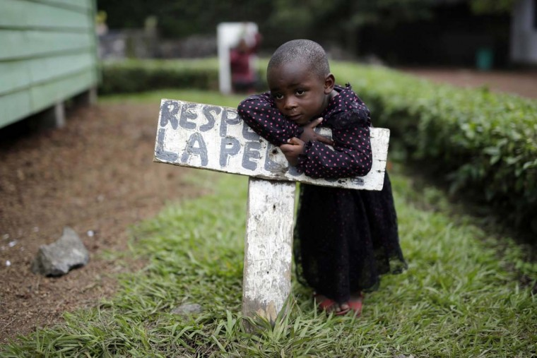 """In this photo taken on Monday, June 20, 2016, Rachel Wanimigabo, three, rests on a sign reading """"respect the grass"""" at the En Avant Les Enfants INUKA center in Goma, Democratic Republic of Congo. Rachel's mother died giving birth to her youngest brother in April 2016. Her father disappeared. (AP Photo/Jerome Delay)"""