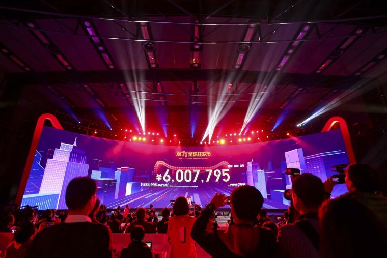 """Attendees watch the start of the Singles Day online shopping festival just past midnight with a screen showing the transaction volume in Shenzhen in southern China's Guangdong province Friday, Nov. 11, 2016. China's online shoppers are engaging in a rare bright spot for its cooling economy - a quirky holiday dubbed """"Singles Day"""" that has grown into the world's busiest day for e-commerce. The country's biggest e-commerce brand, Alibaba Group, said Friday sales by the thousands of retailers on its platforms passed 62.6 billion yuan ($9 billion) in the first 10 hours of the day. (Chinatopix Via AP)"""