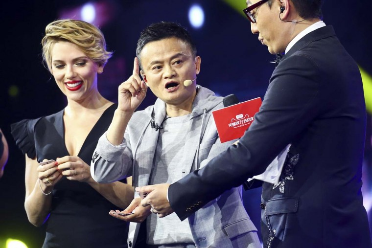 """In this Thursday, Nov. 10, 2016 photo, Hollywood actress Scarlett Johansson, left, and Alibaba Group Chairman Jack Ma, center, attend an evening gala on the eve of the Singles Day online shopping festival in Shenzhen in southern China's Guangdong province. China's online shoppers are engaging in a rare bright spot for its cooling economy — a quirky holiday dubbed """"Singles Day"""" that has grown into the world's busiest day for e-commerce. The country's biggest e-commerce brand, Alibaba Group, said Friday sales by the thousands of retailers on its platforms passed 62.6 billion yuan ($9 billion) in the first 10 hours of the day. (Chinatopix Via AP)"""