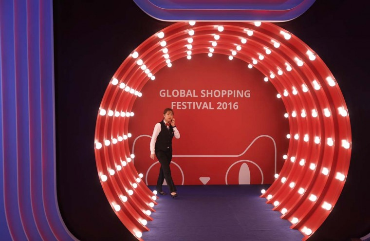 """A woman walks at an exhibition during the """"Singles' Day"""" global online shopping festival in Shenzhen, southern China's Guangdong province Friday, Nov. 11, 2016. In a bright spot for China's cooling economy, online shoppers spent billions of dollars Friday on """"Singles Day,"""" a quirky holiday that has grown into the world's busiest day for e-commerce. (AP Photo/Kin Cheung)"""