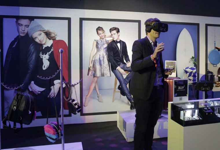 """A man wearing a viewer headset experiences augmented reality intelligent for shopping at an exhibition during the """"Singles' Day"""" global online shopping festival in Shenzhen, southern China's Guangdong province Friday, Nov. 11, 2016. In a bright spot for China's cooling economy, online shoppers spent billions of dollars Friday on """"Singles Day,"""" a quirky holiday that has grown into the world's busiest day for e-commerce. (AP Photo/Kin Cheung)"""