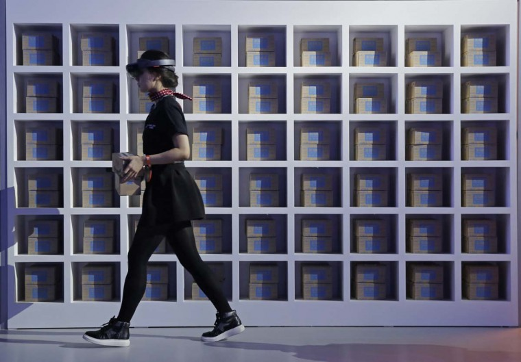 """An attendant wearing a viewer headset, matches the boxes as she demonstrates the augmented reality intelligent at an exhibition during the """"Singles' Day"""" global online shopping festival in Shenzhen, southern China's Guangdong province Friday, Nov. 11, 2016. In a bright spot for China's cooling economy, online shoppers spent billions of dollars Friday on """"Singles Day,"""" a quirky holiday that has grown into the world's busiest day for e-commerce. (AP Photo/Kin Cheung)"""