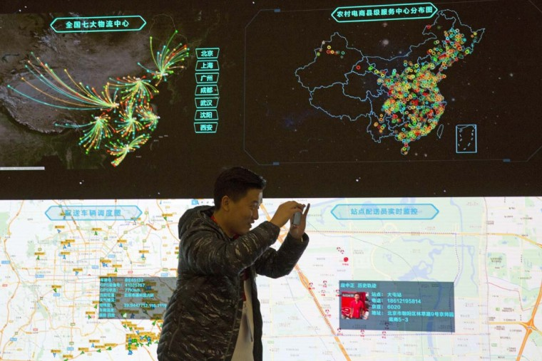 """A Chinese man takes photos with his mobile phone near a display showing the movement of packages around China at the JD.com command center in Beijing, China, Friday, Nov. 11, 2016. In a bright spot for China's cooling economy, online shoppers spent billions of dollars Friday on """"Singles Day,"""" a quirky holiday that has grown into the world's busiest day for e-commerce. (AP Photo/Ng Han Guan)"""