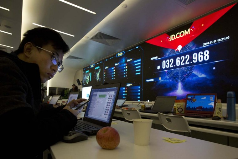 """A Chinese worker looks up near screens displaying the movement of packages around China at the JD.com command center in Beijing, China, Friday, Nov. 11, 2016. In a bright spot for China's cooling economy, online shoppers spent billions of dollars Friday on """"Singles Day,"""" a quirky holiday that has grown into the world's busiest day for e-commerce. (AP Photo/Ng Han Guan)"""