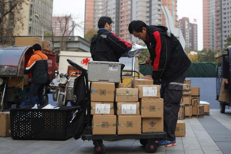 """Delivery workers sort parcels for their customers in Beijing, Friday, Nov. 11, 2016. In a bright spot for China's cooling economy, online shoppers spent billions of dollars Friday on """"Singles Day,"""" a quirky holiday that has grown into the world's busiest day for e-commerce. (AP Photo/Andy Wong)"""