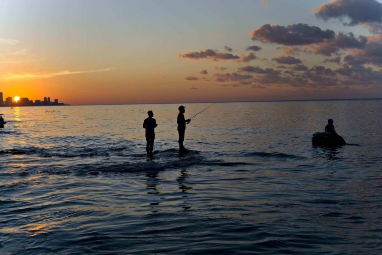 In this Nov. 11, 2016 photo, fishermen stand in the water as a man on a foam raft fishes for bait, off Chivo beach in Havana, Cuba. Cuba has been renowned for its fishing at least since the days of Ernest Hemingway, and foreigners by the thousands come each year to fish in waters largely protected by Cuba's lack of development. (AP Photo/Ramon Espinosa)