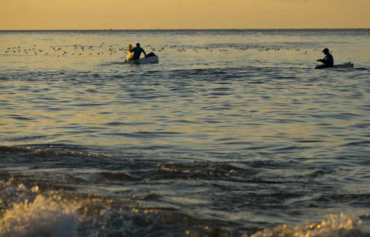 "In this Nov. 11, 2016 photo, young fishermen float on foam rafts to fish for bait off Chivo beach in Havana, Cuba. Many Cubans have taken to riding out on inner tubes or blocks of industrial foam to catch larger fish, but the unsafe technique known as ""cork fishing,"" has become the target of frequent coast guard crackdowns with steep fines. (AP Photo/Ramon Espinosa)"