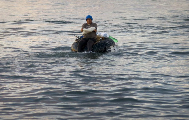 "In this Nov. 11, 2016 photo, a fisherman floats on his raft made out of a tire inner tube, off Chivo beach in Havana, Cuba. Many Cubans have taken to riding out on inner tubes to catch larger fish, but the unsafe technique known as ""cork fishing,"" has become the target of frequent coast guard crackdowns with steep fines. (AP Photo/Ramon Espinosa)"