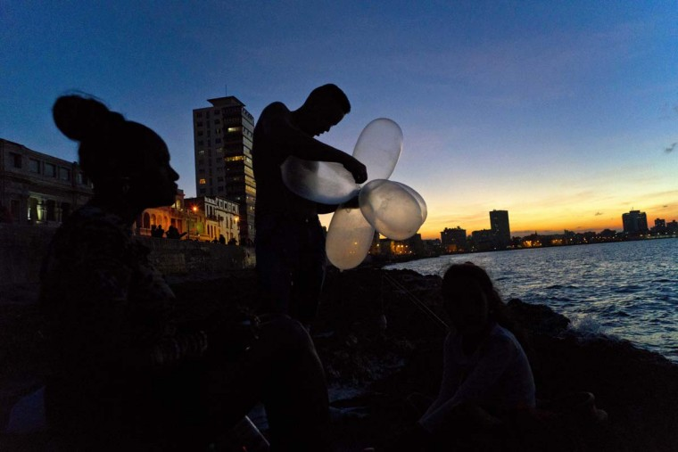 "In this Nov. 13, 2016 photo, mechanic Junior Torres Lopez ties inflated condoms together for his fishing line to keep his bait high in the water and increase his line's resistance against the pull of heavy fish, as his wife Edelmis Ferro Solano sits nearby along the malecon sea wall, at sunset in Havana, Cuba. Dozens of men can be found ""balloon fishing"" along the Havana seawall at night, using their homemade floats to carry their lines as far as 900 feet into the coastal waters. (AP Photo/Ramon Espinosa)"
