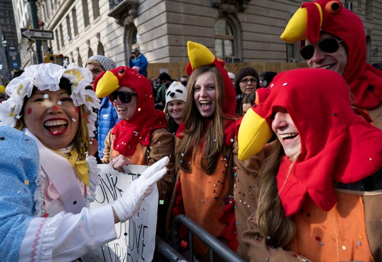 A parade participant tosses confetti on, from center left, Annie Quinn, Lauren Quinn, Mark Rossman and Abby Quinn, all of Albany, New York, during the Macy's Thanksgiving Day Parade in New York Thursday, Nov. 24, 2016. The Quinns are sisters and Rossman is their cousin. (AP Photo/Craig Ruttle)