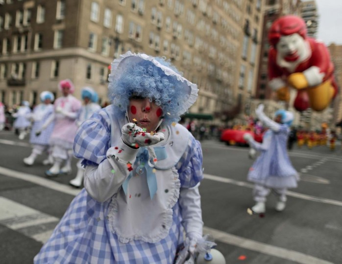 A clown blows confetti toward spectators during the Macy's Thanksgiving Day parade, Thursday, Nov. 24, 2016, in New York. (AP Photo/Julie Jacobson)