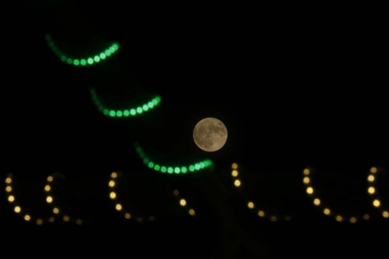 "A picture taken on November 14, 2016 shows the moon seen past decorative lights on the eve of the ""supermoon"" spectacle in Gaza City. (Mohammed ABED/AFP/Getty Images)"
