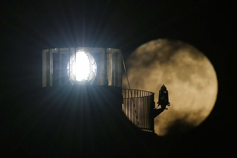 """A Supermoon rises behind a lighthouse in Vilanova i la Geltru near Barcelona on November 14, 2016. The phenomenon happens when the moon is full at the same time as, or very near, perigee -- its closest point to Earth on an elliptical, monthly orbit. It was the closest to Earth since 1948 at a distance of 356,509 kilometres (221,524 miles), creating what NASA described as """"an extra-supermoon"""". (LLUIS GENE/AFP/Getty Images)"""