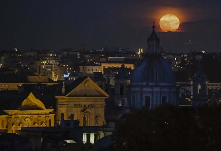 A full moon rises over the Rome's skyline, Monday, Nov. 14, 2016. Monday's supermoon, a phenomenon that happens when the moon is visible in full as it makes a close pass at the earth, is the closest to earth since 1948. (Alessandro Di Meo/ANSA via AP)