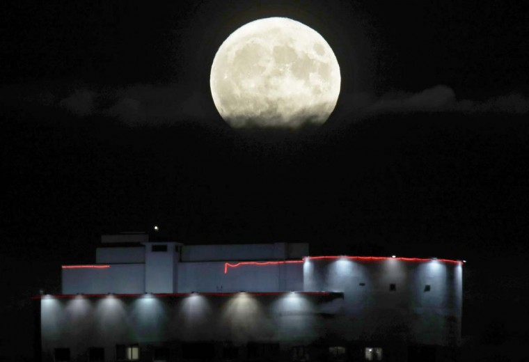 The moon rises from behind the top of an apartment building in Minsk , Belarus, Monday, Nov. 14, 2016. The brightest moon in almost 69 years will be lighting up the sky this week in a treat for star watchers around the globe. (AP Photo/Sergei Grits)