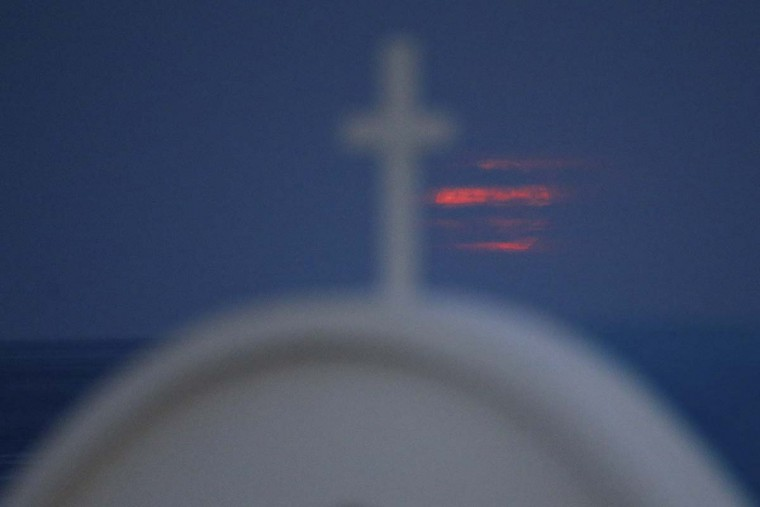 "The moon is seen through the clouds as it rises over the Mediterranean sea behind a cross on the ""Ayious Saranta"" church in Cape Greco at the eastern part of the island of Cyprus, Monday, Nov. 14, 2016. The brightest moon in almost 69 years, a phenomenon known as the supermoon, is lighting up the sky in a treat for star watchers around the globe. (AP Photo/Petros Karadjias)"