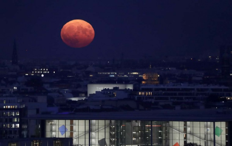 The moon rises behind the golden dome of the New Synagogue and the Paul-Loebe-Haus, front, a lawmaker office building of the German federal parliament, in Berlin, Germany, Monday, Nov. 14, 2016. The brightest moon in almost 69 years is lighting up the sky in a treat for star watchers around the globe. (AP Photo/Michael Sohn)