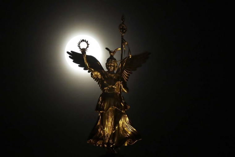 The moon rises behind the victory column in Berlin, Germany, Monday, Nov. 14, 2016. The brightest moon in almost 69 years is lighting up the sky in a treat for star watchers around the globe. (AP Photo/Michael Sohn)