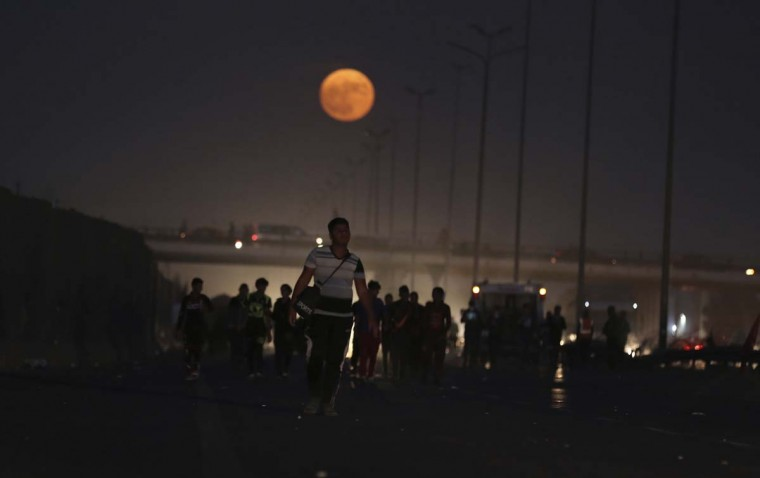 "The moon rises over Shiite pilgrims as they march to Karbala for the Arbaeen ritual in Baghdad, Iraq, Monday, Nov. 14, 2016. The brightest moon in almost 69 years lit up the sky, during its closest approach to earth as the ""Supermoon"" reached its most luminescent phase. The moon won't be this close again until Nov. 25, 2035. (AP Photo/Hadi Mizban)"