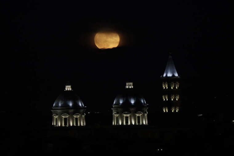 """The moon rises over St. Mary Major Basilica in Rome, Monday, Nov. 14, 2016. The brightest moon in almost 69 years lit up the sky, during its closest approach to earth as the """"Supermoon"""" reached its most luminescent phase. The moon won't be this close again until Nov. 25, 2035. (AP Photo/Gregorio Borgia)"""