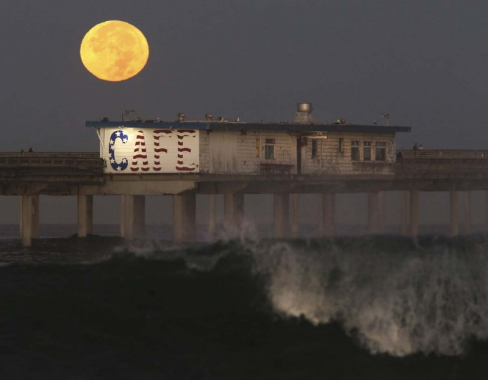 "A ""supermoon"" sets behind Ocean Beach Pier Monday morning, Nov. 14, 2016, while dozens of photographers got up early to watch. The moon appears about 7% larger than normal and about 15% brighter during it's full phase through Monday night, although the human eye is barely able to discern that difference. The moon hasn't been this close to the Earth since 1948. It won't be this close again until November 25, 2034. (Peggy Peattie/San Diego Union-Tribune via AP) /The San Diego Union-Tribune via AP)"