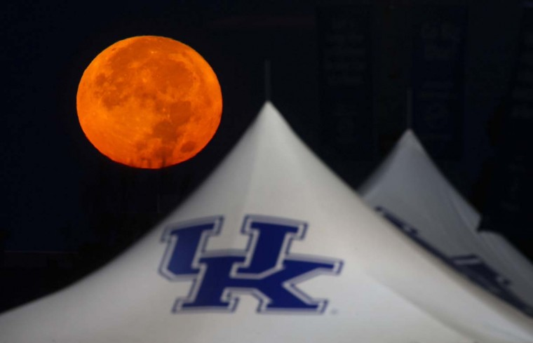 "The ""supermoon"" sets behind a tailgating tent in the parking lot of Commonwealth Stadium on the University of Kentucky parking lot Nov. 14, 2016 in Lexington Ky. (Charles Bertram/Lexington Herald-Leader/TNS)"
