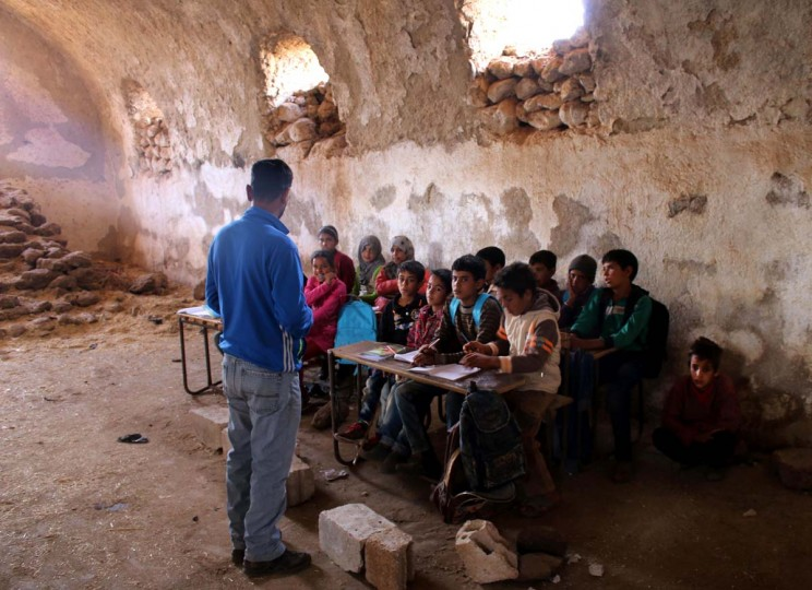 A Syrian teaches children during class in a barn that has been converted into a makeshift school to teach internally displaced children from areas under government control, in a rebel-held area of Daraa, in southern Syria on November 10, 2016. Rebels hold most of Daraa province, but the regional capital is largely controlled by the government. (MOHAMAD ABAZEED/AFP/Getty Images)