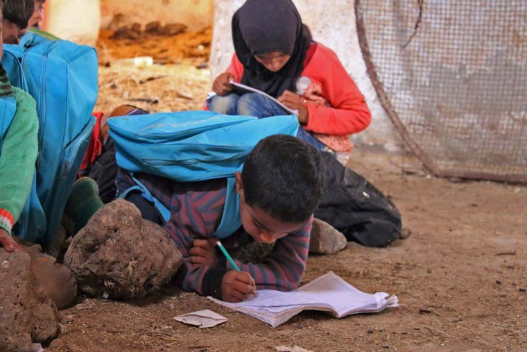 A Syrian boy writes in a notebook while on the ground in class in a barn that has been converted into a makeshift school to teach internally displaced children from areas under government control, in a rebel-held area of Daraa, in southern Syria on November 10, 2016. The school has a shortage of seats prompting many children to sit on stones instead. Rebels hold most of Daraa province, but the regional capital is largely controlled by the government. (MOHAMAD ABAZEED/AFP/Getty Images)